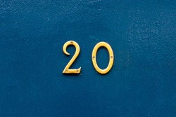 House number 20 in thin bronze metal numbers - the twenty is on a blue wooden front door