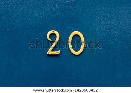 House number 20 in thin bronze metal numbers - the twenty is on a blue wooden front door Сток-фото ©