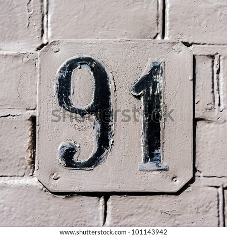 house number ninety-one on a metal late, clumsy over-painted