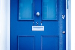 House number 127 on a blue wooden front door with letterbox