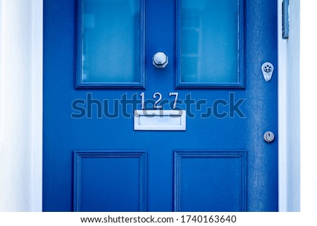 House number 127 on a blue wooden front door with letterbox Stock photo ©