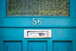 House number 56 on a blue wooden front door with shiny letterbox and glass