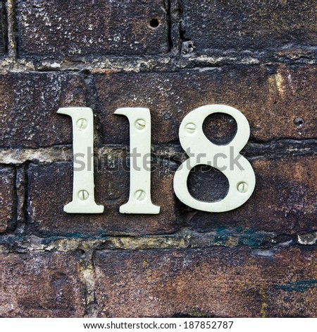 house number one hundred and eighteen on a brick wall