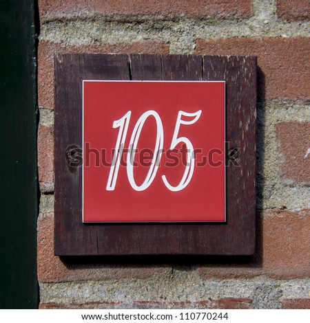 House number one hundred and five engraved in a red formica plate