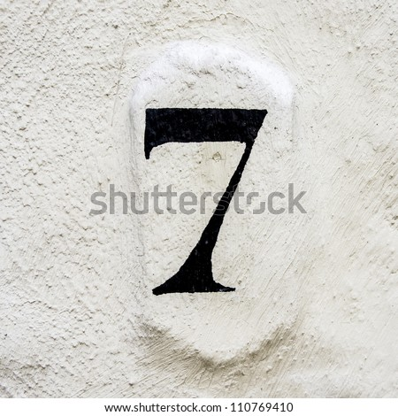 house number seven painted on a white plastered wall