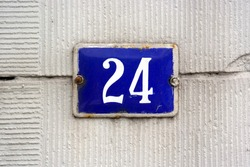 House Number 24 sign. Blue enamelled Number twenty-four plate mounted on a stucco wall.