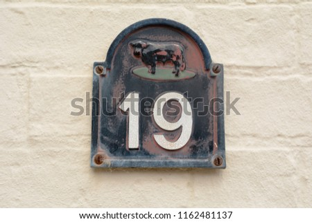 House number 19 sign with cow on wall