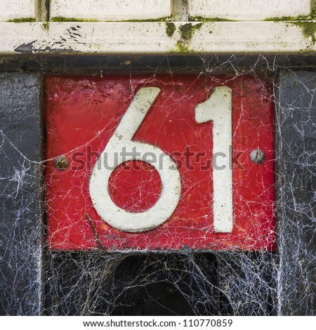 house number sixty-one covered by a cobweb. White lettering on a red background