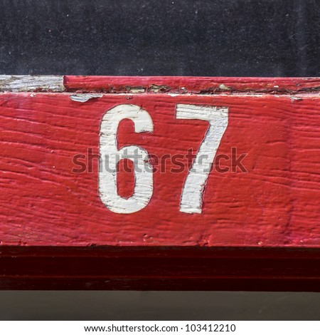 house number sixty-seven, on a red painted door post