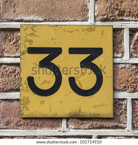 house number thirty-three, engraved in a gold colored plastic plate