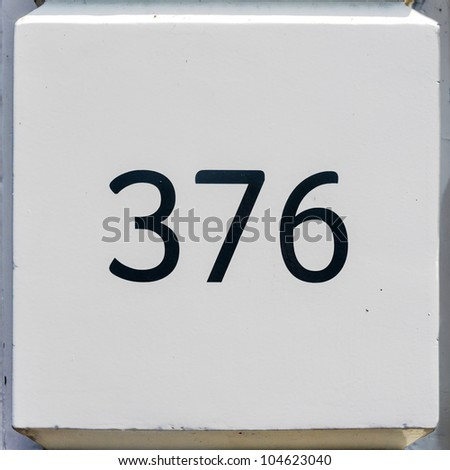 house number three hundred and seventy-six on a white wall segment