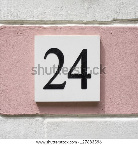 House number twenty four. Black lettering on a white plate on a pink wall.