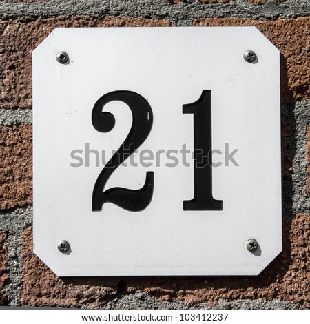 house number twenty-one. Black lettering on a white plate, attached to a brick wall