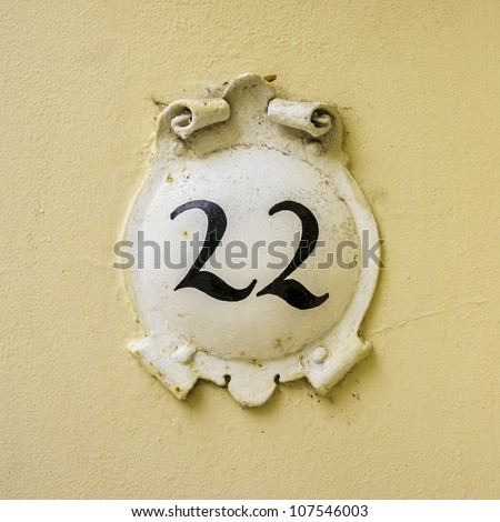 house number twenty-two on a round plate surrounded by curly ornaments