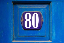 House number 80 with the eighty on a blue enamel sign on a blue wooden front door