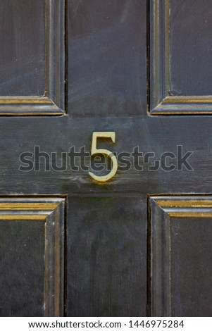 House number 5 with the five in bronze on a black wooden front door with panels edged in gold