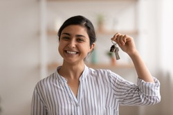 House of dream. Headshot portrait of excited indian female happy winner buyer renter tenant of new home apartment. Young mixed race woman proud homeowner looking at camera showing keys of modern flat
