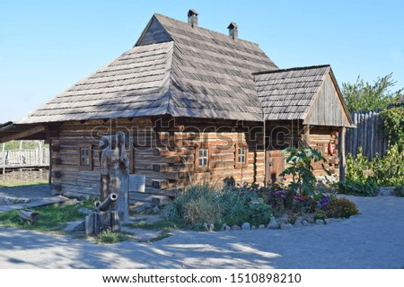 House of wooden log cabins and tiled roof against a blue sky. Entrance to a wooden house with wooden flooring. Ancient building of the 18th century in Zaporizhia, Ukraine. stock photo