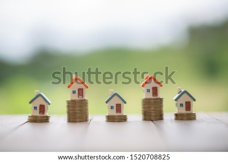 House on a pile of coins Real estate concept Mortgages and investments, save money or invest for a future home, choosing a home, buying and selling a house. There is a text input area.