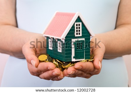 House on a pile of golden coins in woman hands