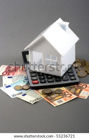 House on top of a calculator and money over gray background