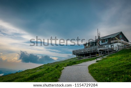 Stock Photo House on top of a mountain with clouds and sunset on the background