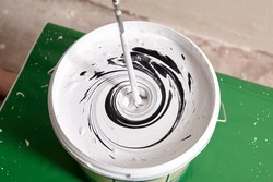 House painter mixes two paints using mixer for bucket with paddle mixing tool.