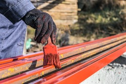 House painter paints metal structures. Protective coating of steel closed profiles with primer iron oxide red.