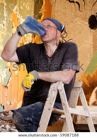 House Painter sitting of the ladder and drinking water