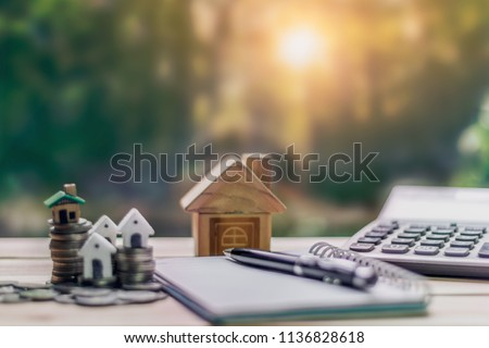 House placed on coins. notebook and pen Prepare planning savings money of coins to buy a home concept for property ladder, mortgage and real estate investment. for saving or investment for a house.