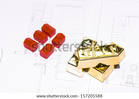 House plans with gold bullion and red toy houses.