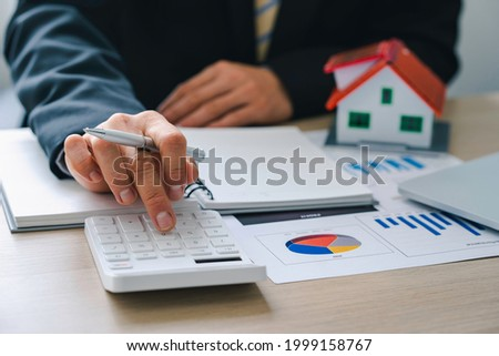 House plans with real estate agents and clients calculating the first lump sum for a home purchase contract, insurance or real estate loan Foto stock ©