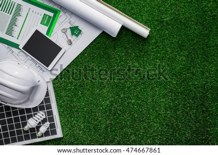 House project, solar panel and protective helmet on lush grass, green sustainable building and alternative energies concept