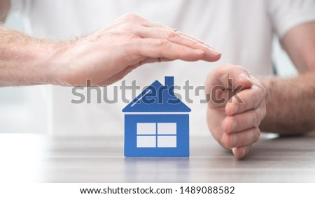 House protected by hands - Concept of home insurance #1489088582