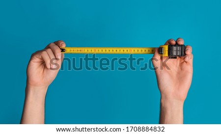 House renovation concept. Unrecognizable repairman holding tape measure on blue background, closeup. Panorama ストックフォト ©