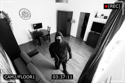 house robbery - burglar captured on surveillance security camera in living room