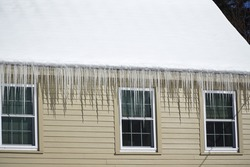 house roof with icicle hanging in winter