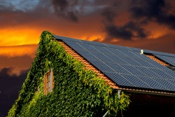 house roof with solar panels and a beautiful sunset