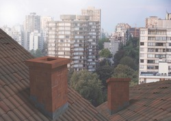 House Roofs with chimney contrasting with apartment blocks