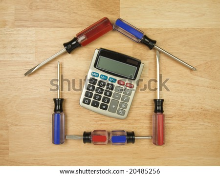 House Shaped by Screwdrivers and Calculator on a Wood Background.