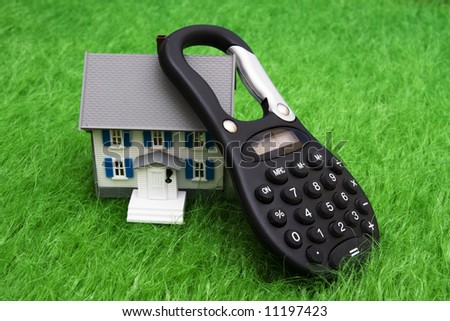 House sitting on grass with calculator