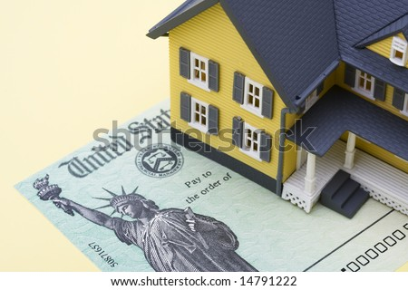 House sitting on sitting beside a tax refund check - stock photo