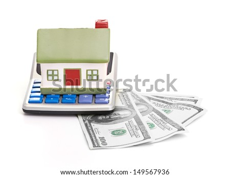 house sitting with a calculator and dollar - stock photo