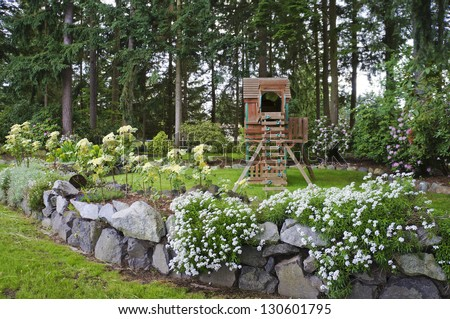 House spring backyard with rock wall and kids playground with wooden swing and slide.