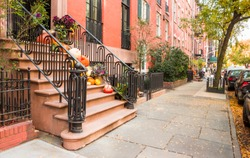 House steps and entrance decorated for Halloween with pumpkins in West Village, Manhattan, New York