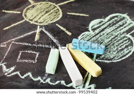 House, sun and tree drawing and chalks on a blackboard
