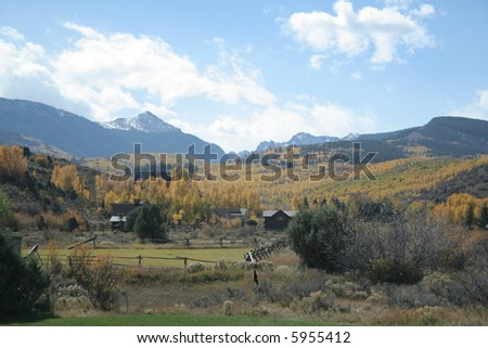House surrounded by autumn aspens that are yellow and snowy mountain peak