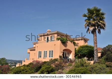 House surrounded by trees and blue sky. Orange color. Large palm tree in the back. Patio area in back.