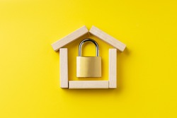 house symbol made by wooden blocks over yellow background with padlock inside. outer space. home protection and security concept.