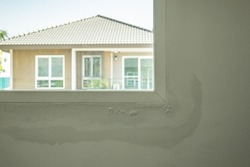 house wall near the window with some water stain show peeling paint